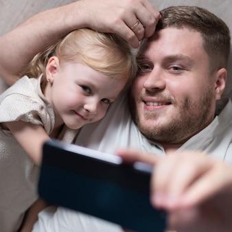 Vater und tochter, die zu hause selfie nehmen