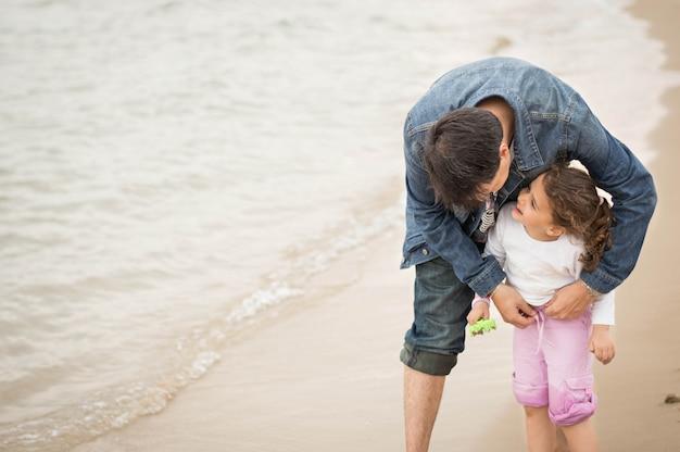 Vater und tochter, die zusammen einen tag am strand genießen.