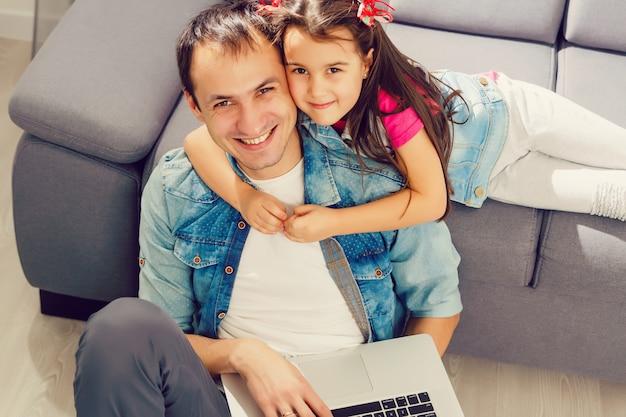 Vater und tochter, die zusammen laptop zu hause verwenden