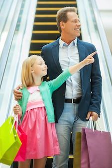 Vater und tochter einkaufen. fröhlicher vater und tochter, die mit der rolltreppe nach unten fahren und einkaufstüten halten