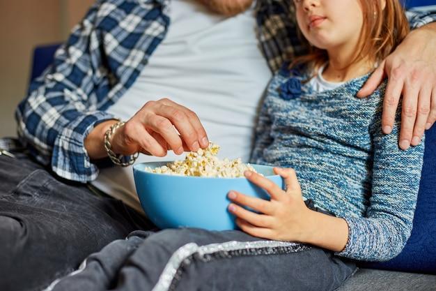 Vater und tochter essen popcorn und schauen sich einen fernsehfilm an, vater und kind schauen sich zu hause einen film auf einer couch an