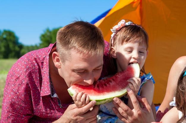 Vater und tochter essen wassermelone beim picknick