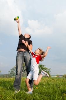 Vater und tochter fangen den ball