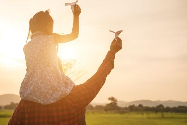 Vater und tochter freuen sich über das papierflugzeug auf der wiese.