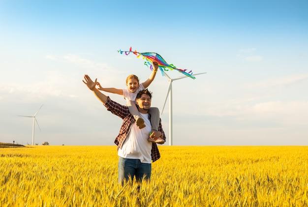 Vater und tochter haben spaß und spielen zusammen mit dem drachen auf dem weizenfeld am hellen sommertag