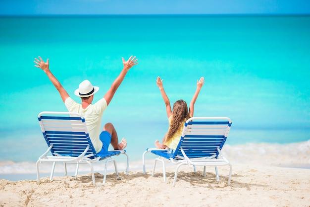 Vater und tochter hände oben am strand sitzen auf chaiselongue