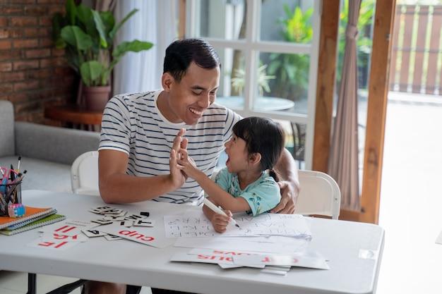 Vater und tochter high five beim gemeinsamen lernen zu hause