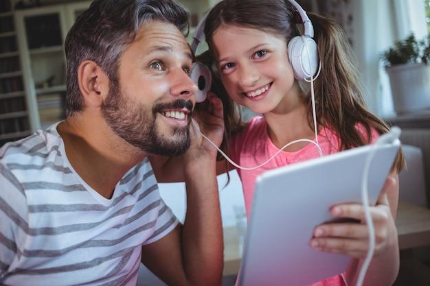 Vater und tochter hören musik auf digitalem tablet
