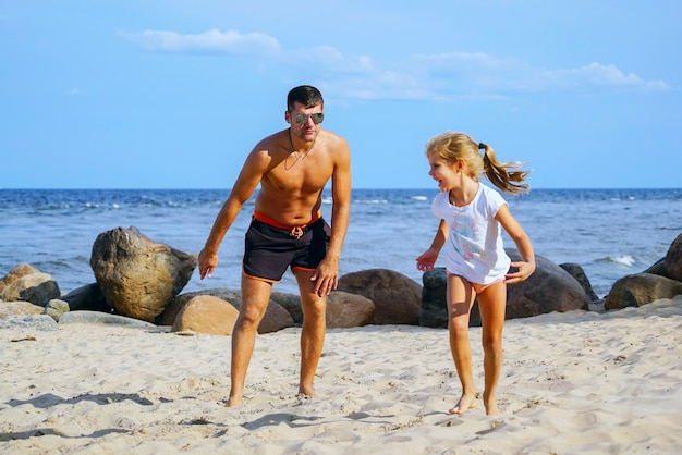 Vater und tochter holen am strand auf.