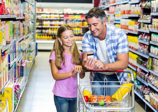Vater und tochter im supermarkt unter verwendung des smartphone