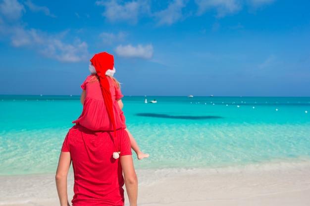 Vater und tochter in santa hat am tropischen strand