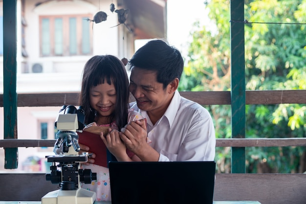 Vater und tochter lächeln und lernen von zu hause mit laptop und mikroskop