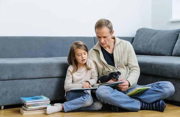 Vater und tochter lesen bücher. der welpe liegt auf den beinen des mannes.