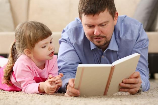 Vater und tochter liegen auf dem boden und lesen zusammen ein interessantes buch