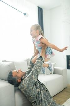 Vater und tochter. mann, der nach dem militärdienst nach hause kommt und sich beim spielen mit tochter fröhlich fühlt