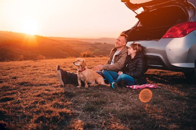 Vater und tochter mit dem hund, der auf einem hügel durch das auto während des sonnenuntergangs kampiert