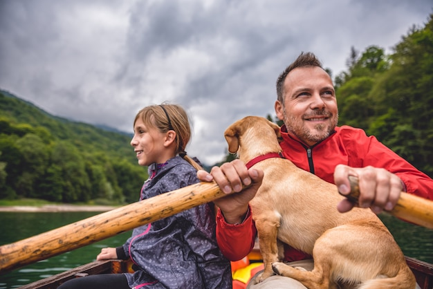 Vater und tochter mit einem hund, der ein boot rudert
