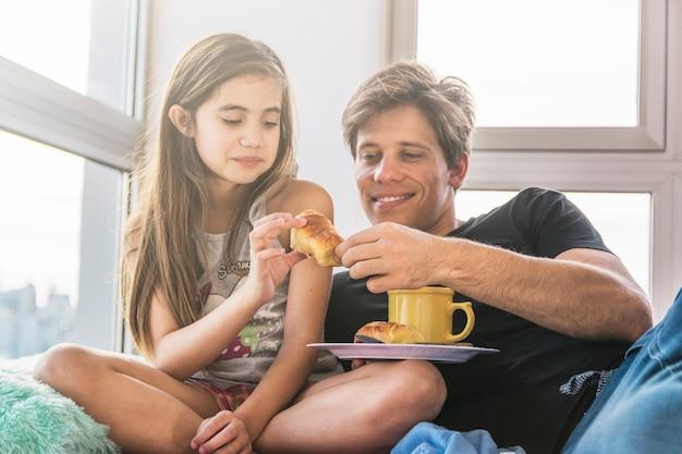 Vater und tochter mit tasse tee und brot während des frühstücks