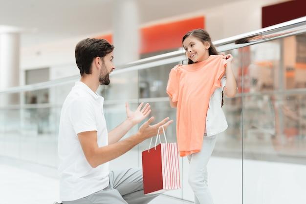 Vater und tochter nehmen neue strickjacke im mall heraus