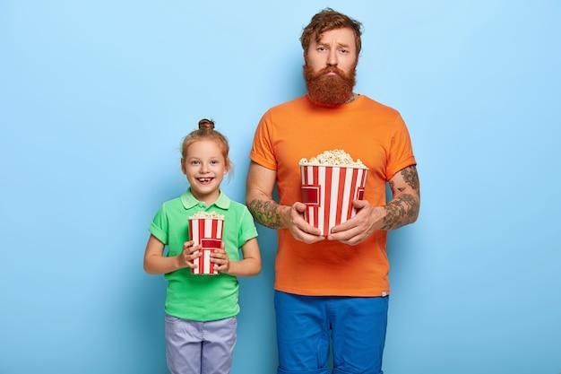 Vater und tochter posieren mit popcorn