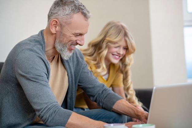 Vater und tochter schauen sich etwas auf einem laptop an
