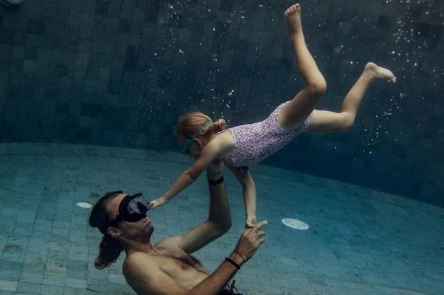 Vater und tochter schwimmen zusammen im pool