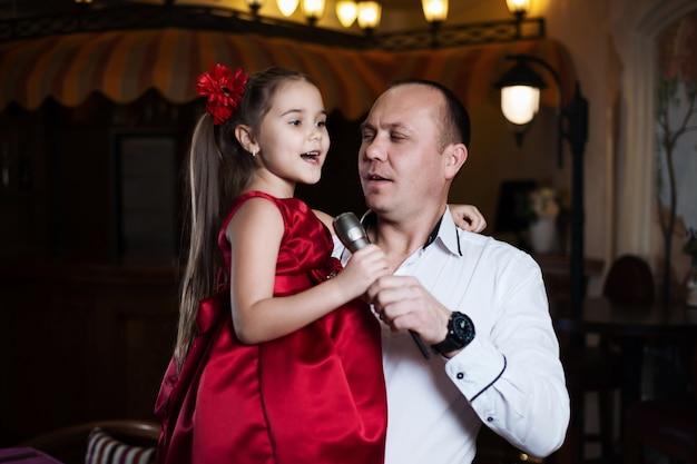 Vater und tochter singen ein karaoke-lied ins mikrofon