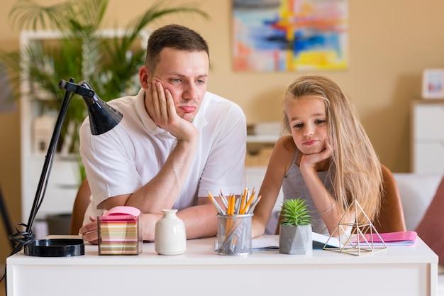Vater und tochter sitzen an einem schreibtisch