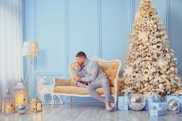 Vater und tochter sitzen auf einem sofa neben dem weihnachtsbaum. weihnachtsfoto-session.