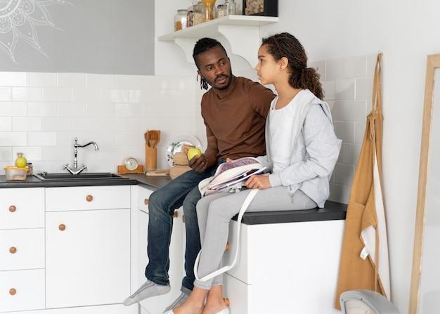 Vater und tochter sitzen auf einer küchentheke