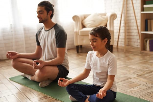 Vater und tochter sitzen in lotus pose on carpet.