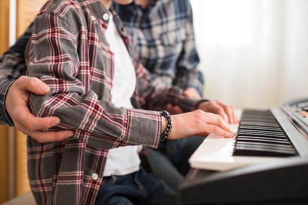 Vater und tochter spielen am klavier