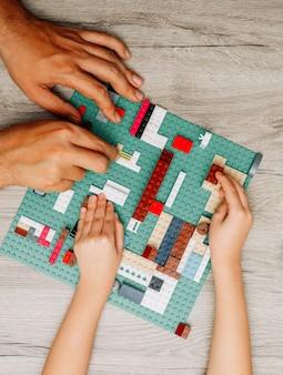 Vater und tochter spielen mit legos auf hellem holz