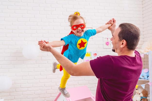 Vater und tochter spielen superhelden.