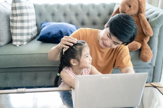 Vater und tochter spielen zu hause mit notebook-computer
