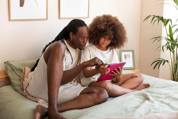 Vater und tochter spielen zusammen auf einem tablet