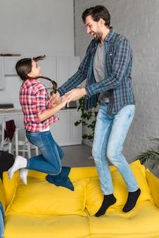 Vater und tochter springen auf das sofa