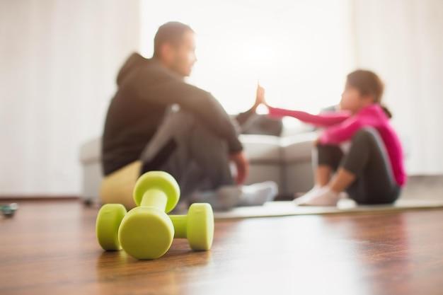 Vater und tochter trainieren zu hause. training in der wohnung. sport zu hause. sie sitzen auf yogamatten und geben sich gegenseitig fünf. im vordergrund stehen hanteln.