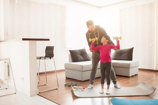 Vater und tochter trainieren zu hause. training in der wohnung. sport zu hause. sie stehen auf einer yogamatte. mädchen, das hantel hält.