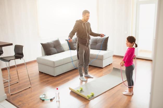 Vater und tochter trainieren zu hause. training in der wohnung. sport zu hause. sie verwenden ein gummiseil zum training.