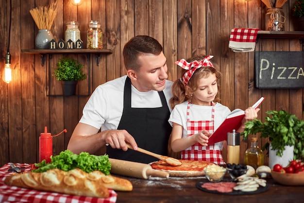 Vater- und tochterleserezeptbuch beim kochen der pizza