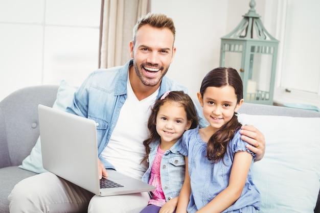 Vater und töchter mit dem laptop, der auf sofa sitzt