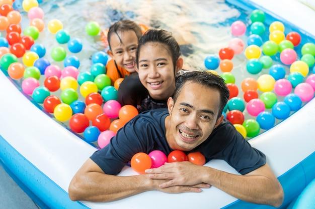 Vater und töchter spielen in einem schwimmbad
