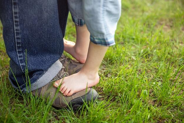 Vater unterstützt den kleinen sohn. entzückende füße auf dem boden in der natur.