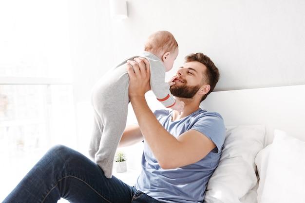 Vater vater des jungen mannes, der spaß mit seinem kleinen baby hat