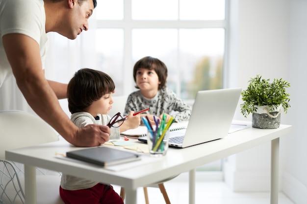 Vater verbringt zeit zusammen mit seinen kindern zu hause. kleine lateinamerikanische jungs spielen zusammen und zeichnen bilder, die am tisch sitzen. selektiver fokus