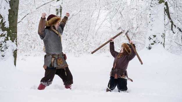 Vater wikinger mit seinem sohn im winterwald. vater bringt seinem sohn das kämpfen bei und hält die axt in der hand. sie trugen mittelalterliche kleidung.