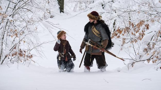 Vater wikinger mit seinem sohn in den winterwald gehen, sie haben axt, speer, zwiebel.