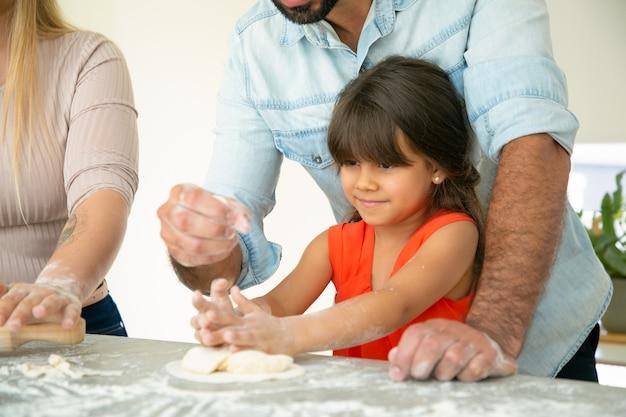 Vater zeigt tochter, wie man teig auf küchentisch mit mehl unordentlich macht. junges paar und ihr mädchen backen brötchen oder kuchen zusammen. familienkochkonzept