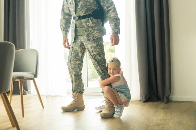 Vaterbein umarmen. kleines blondes mädchen, das ihr vaterbein umarmt, während er das haus zum militärdienst verlässt